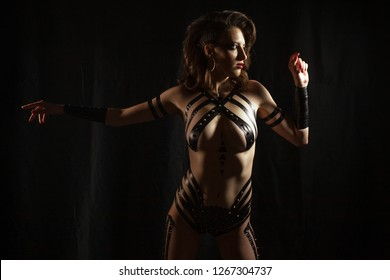 Beautiful Bdsm woman dressed in black costume from tape with metal spikes stands on black background. Concept of domination and bondage.