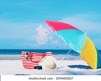 Beautiful beach background with beach bag and umbrella on white sand,copy space.