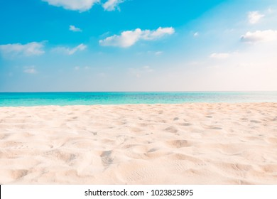 Beautiful beach background. Tropical beach view with soft sand and blue sea and blue sky and fluffy clouds.