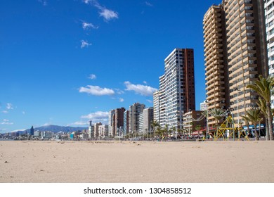 The beautiful beach of Benidorm in Alicante Spain, the beach in locally known as Playa de Levante beach, showing the beach and also high rise hotels and offices on a beautiful blue sky day.