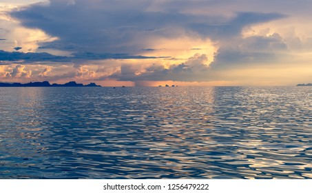Beautiful beach blue sunset with big rain clouds and golden light sky  background
