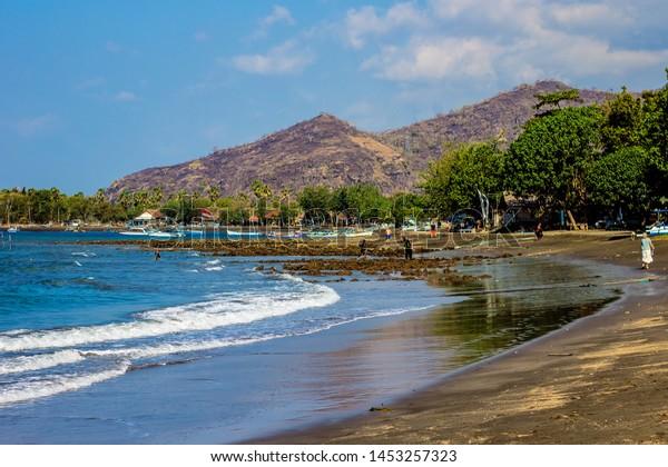 Beautiful beach with dark sand, Bali sea in the background on sunny summer day in Pemuteran, north Bali coastline, Indonesia