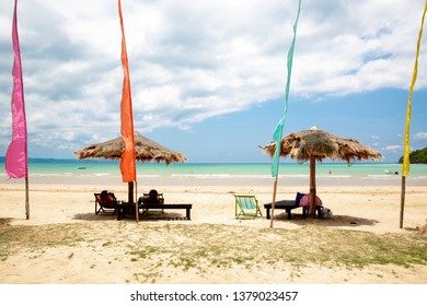 Beautiful beach with deck chair and parasol colorful flag at Ao Kao beach, Koh Mak island, Trat, Thailand