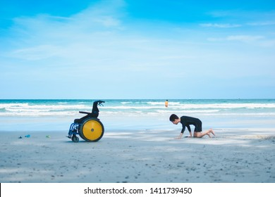 The beautiful beach and disabled child crawling on to his wheelchair, Softly focus, Life in the education age of special Children, Happy disabled kid concept.