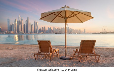 Beautiful beach in Dubai with 2 sun chairs and an umbrella. In the background is the skyline of Dubai Marina