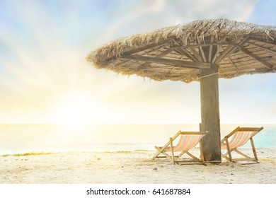 Beautiful beach with empty pair of chaise-lounges under natural straw parasol