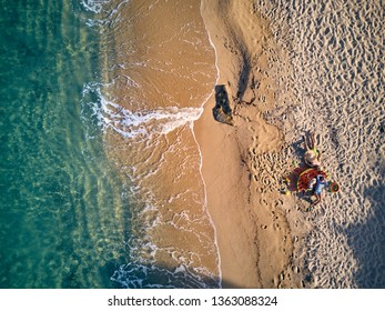 Beautiful beach with family top aerial view drone shot. Summer family vacation. Sithonia, Greece.