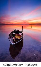 Beautiful beach with fisherman boat during sunrise at Jubakar beach Kelantan, Malaysia. Soft focus due to long exposure.