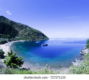 beautiful beach in gorontalo province, Indonesia. U shape beach located in Sulawesi.  White shore with some boats and  warmed sunlight