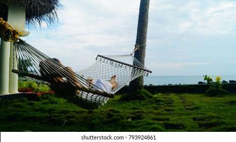 Beautiful beach house with a hammock nearby. Beach hut with a thatched roof. Small yard. Perfect option for romantic holidays. Young girl laying on the hammock. Time to relax, meditation.