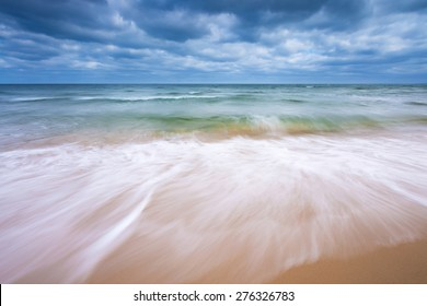 Beautiful beach landscape with cloudy sky and sea with waves. Baltic sea coast near Gdansk in Poland.