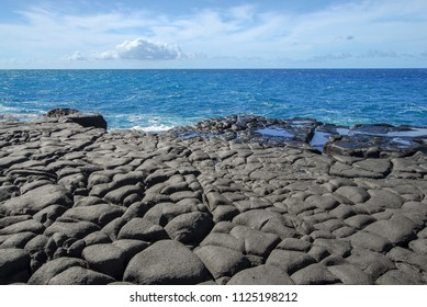 Beautiful beach with lava rock formations on the island of Kauai, Hawaii in the Pacific Ocean