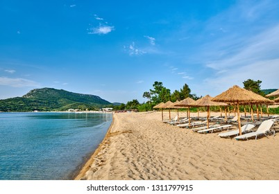 Beautiful beach with loungers and umbrellas in Toroni. Sithonia, Greece