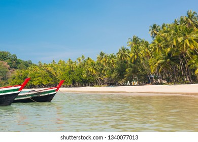 Beautiful beach of Ngapal with fisherman boat and palms hanging over the sea, Myanmar