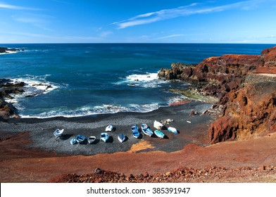 Beautiful beach on the Atlantic Ocean  in the village of El Golfo. A rocky beach with fishing boats surrounded by volcanic mountains / El Golfo bay on the Atlantic Ocean. Lanzarote. Canary Islands