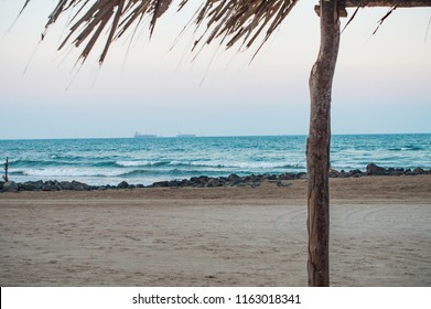 beautiful beach with palapa (thatched roof) and ocean with boats in background, Tuxpan, Veracruz, Mexico.