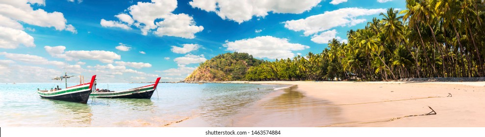 Beautiful beach panorama of Ngapal with fisherman boats and palms hanging over the sea, Myanmar