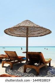Beautiful beach resort with straw umbrellas on a blue sky and white clouds. On the background some people having fun on the beach. Clear sea. Beach life and lifestyle concept. Torre Lapillo, Salento.