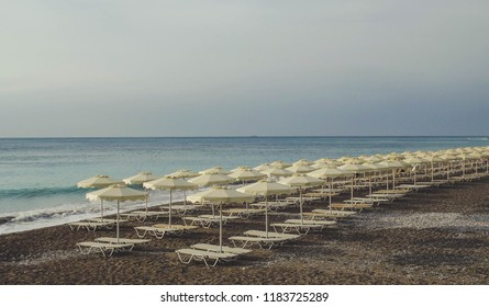 Beautiful beach in Rhodes Island. Sun beds and sun umbrellas at the empty beach. Blue mediterranean sea and grey sky on the background. Rhodes, GREECE.