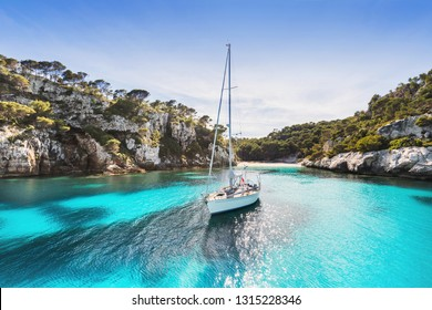 Beautiful beach with sailing boat yacht, Cala Macarelleta, Menorca island, Spain. Yachting, travel and active lifestyle concept