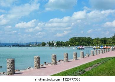 Beautiful beach with sailing boats and paddle boats at the Lake Balaton