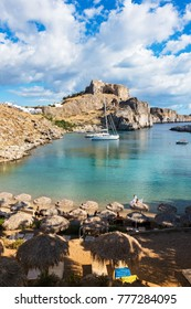 Beautiful beach in St. Paul´s bay, Lindos acropolis in background (Rhodes, Greece)