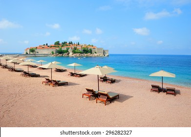 Beautiful beach with sunshades near Sveti Stefan island in Montenegro