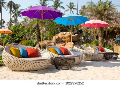 Beautiful beach with swimming pool, coconuts palm trees, rattan daybeds and umbrella in a tropical garden near sea, Thailand