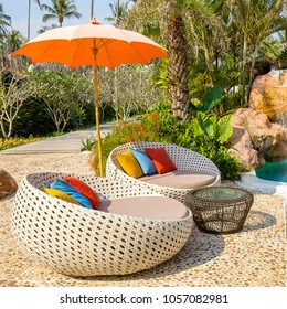 Beautiful beach with swimming pool, green palm trees, rattan daybeds and umbrella in a tropical garden near sea, Thailand