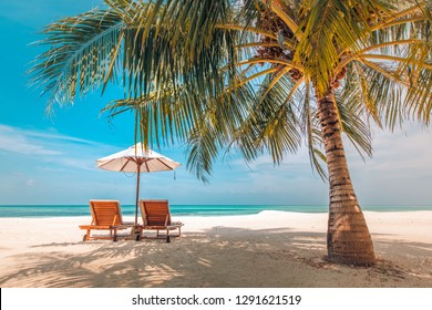Beautiful beach. Tropical landscape with two sun loungers and umbrella under palm tree leaves and sea view. Idyllic scenery, wonderful beach concept for luxury travel and vacation or holiday banner