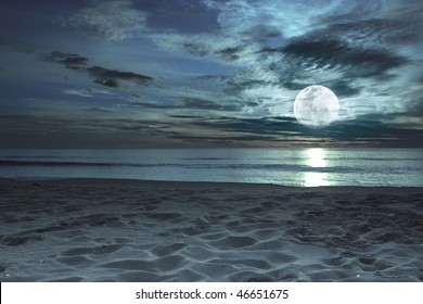 Beautiful beach at twilight time with moon in the sky