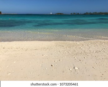 Beautiful beach view of Junkanoo Beach's turquoise waters in the Bahamas with a lighthouse in the far distance.