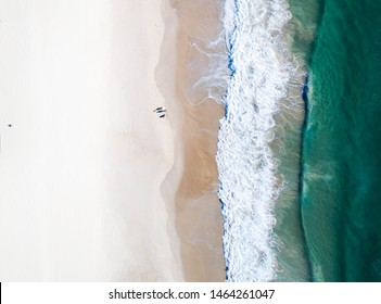Beautiful beach and water at sunrise with people standing in front of wave and on white sand on the Gold Coast. Queensland New South Wales Brisbane Byron Bay Sunshine Coast Noosa Bondi Manly