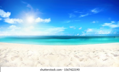 Beautiful beach with white sand, turquoise ocean water and blue sky with clouds in sunny day. Natural background for summer vacation, soft focus.