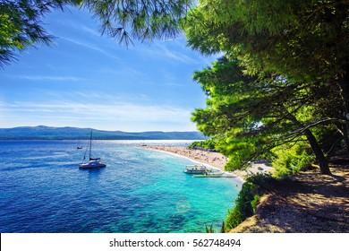 Beautiful beach Zlatni Rat or Golden Cape on island Brac in Croatia with yacht