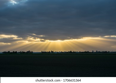 """Beautiful beams of light coming from the sun behind the clouds. Atmospheric phenomenon called """"crepuscular rays""""."""