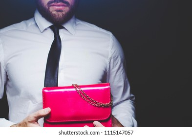 beautiful bearded man holds ladies bag clutch