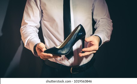 beautiful bearded man in a shirt,holds women's heels