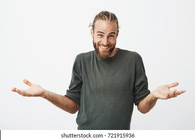 Beautiful bearded man with stylish hairdo smiling and spreading hands don't know what to say in answer. Body language.