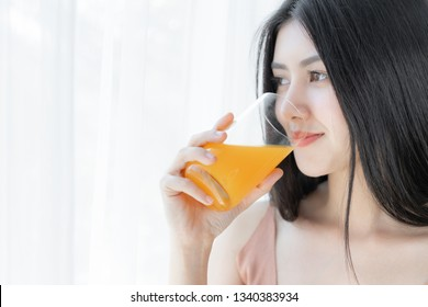 Beautiful beauty woman Asian cute girl feel happy drinking orange juice for good health in the morning , enjoying time in her home  white bedroom background - lifestyle beauty woman concept