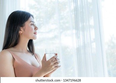 Beautiful beauty woman Asian cute girl feel happy drinking Clean drink water for good health in the morning , enjoying time in her home  white bedroom background - lifestyle beauty woman concept