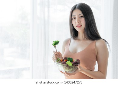Beautiful beauty woman Asian cute girl feel happy eating diet food fresh salad for good health in the morning , enjoying time in her home white bedroom background - lifestyle beauty woman concept