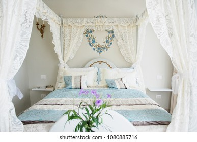 Beautiful Bed With Canopy And Laces In A Hotel Room With Decorated Walls