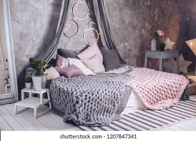 Beautiful bedroom decorated with decorative Christmas elements. Expensive bed with a knitted bedspread