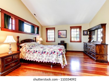 Beautiful bedroom interior with quilted bedding, wood and yellow walls.