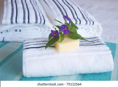 Beautiful bedroom interior with white sheets and striped towels with soap and flowers