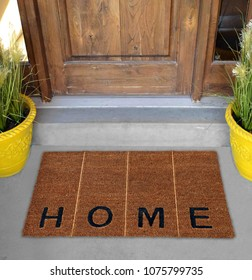 "Beautiful Beige and black zute / coir Outdoor Door mat with ""H O M E"" text and vertical lines outside home with yellow flower pots"