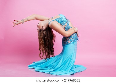 Beautiful belly dancer girl is wearing a blue fashion costume