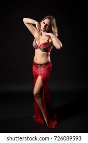 Beautiful belly dancer performing belly dance on black background.Belly dancer