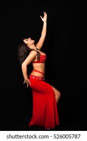 Beautiful belly dancer performing exotic dance , dark background